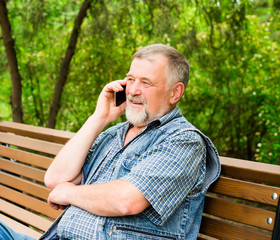 old man on a park bench talking on the phone