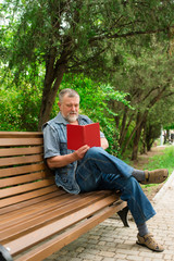 old man reading a book on a park bench