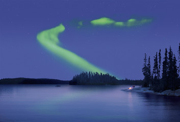 The Northern Lights in the night sky, the Aurora borealis above a calm lake. Two people by a fire on the lake shore.