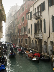 A view of a narrow canal crowded with boats and traditional gondolas, with historic buildings lining the waterfront.