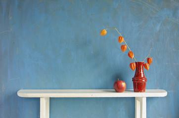 husk tomato  plant flowers in vase on white wooden shelf