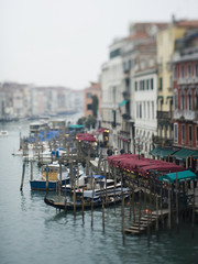 A view from above of a wide canal in Venice, with boats and traditional gondolas moored along the waterfront, and restaurants and cafes.
