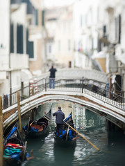 View along a narrow canal, with a person standing on a bridge. A gondola floating below.