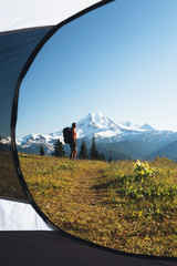 View from inside a camping tent of a man hiking across national forest land with Mount Baker in the distance.