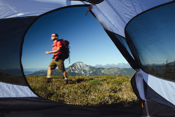View from inside a camping tent of man hiking across national forest land with Mount Baker in the distance.