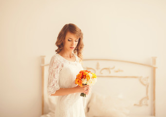 young woman with flowers standing in a bright room