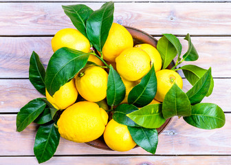 Lemons with leaves in plate on rustic wood table.Citrus fruit.
