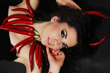 Devil brunette girl with red cayennes peppers