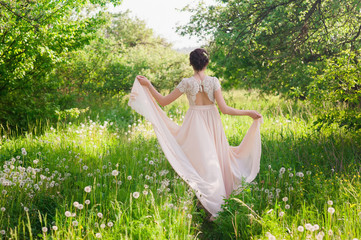 Young beautiful bride standing with his back in park