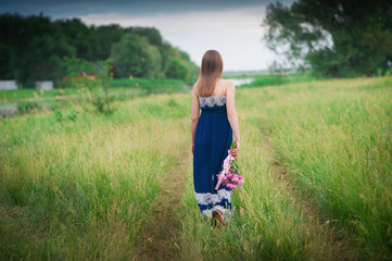 Young beautiful girl with a bouquet of peonies is in the field