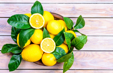 Lemons with leaves on rustic wood background.Citrus fruits.