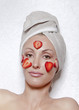 beautiful young woman in towel with a strawberry cosmetic mask