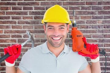 Happy repairman holding hammer and drill machine
