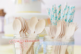 Close up of wooden cutlery and paper straws arranged in jam jars