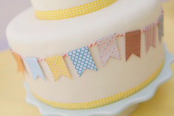 Close up of cake in fondant decorated with buntings and ribbon