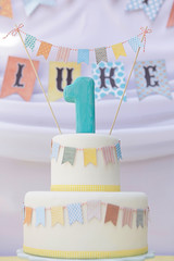 Tiered cake covered in white fondant, decorated with buntings