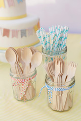 Wooden cutlery and paper straws arranged in jam jars