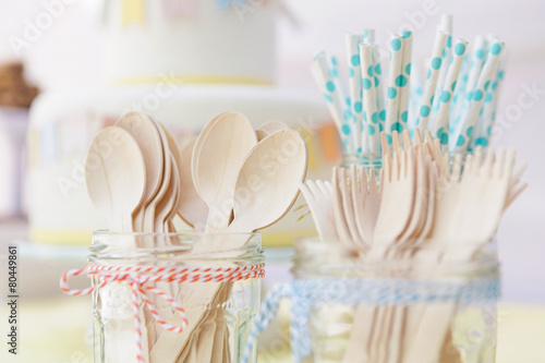 canvas print picture Close up of wooden cutlery and paper straws arranged in jam jars