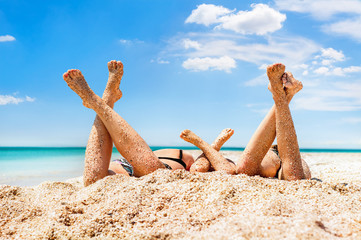 Legs of girls lying on sandy beach