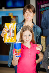 Happy Mother And Daughter Holding Snacks At Cinema