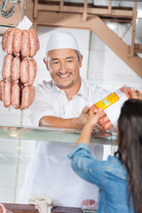 Man Giving Packed Sausages To Female Customer