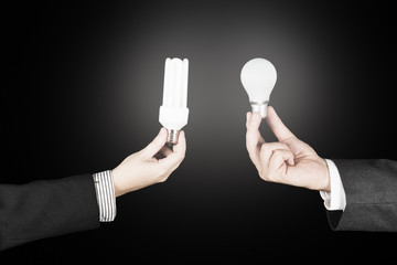 Businessman and businesswoman holding light bulbs