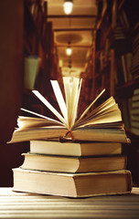 Stack of books on table on bookshelves background