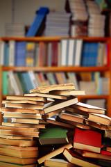 Many books on table on bookshelves background