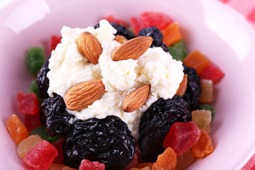 Dessert with prunes with dried fruits in bowl, macro view