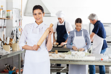 Female Chef Holding Rolling Pin While Colleagues Preparing Pasta