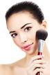Beautiful girl with a makeup brush