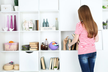 Woman looking for something in closet, in room with modern