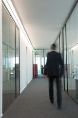 Business man walks in a hallway