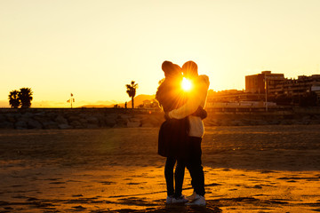 Couple is kissing at the sunset on the beach