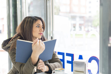 Beautiful pensive woman with book in restaurant looking away.