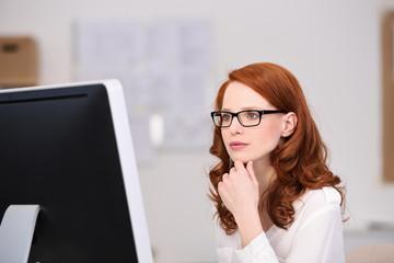 konzentrierte junge geschäftsfrau schaut auf pc