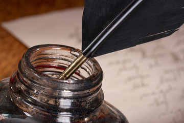 Close-up of a Quill and Inkwell. Handwritten Letter in the Back.