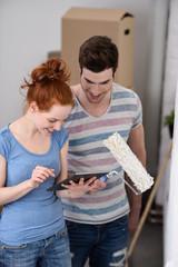 paar beim einzug in neue wohnung schaut auf tablet