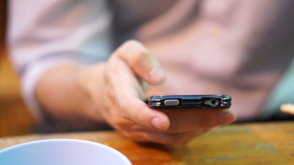 Detail view of Hand using smartphone at restaurant