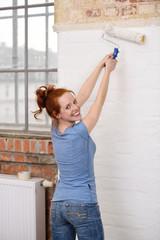 lächelnde frau streicht backsteinwand weiß