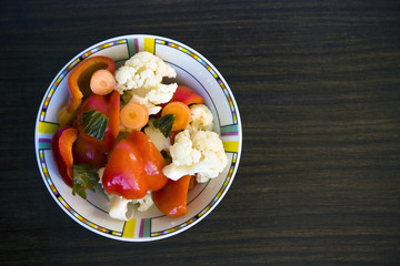 Colorful marinated vegetables on dark table