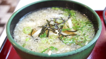 Detail view of Udon soup with tempura topping in green bowl