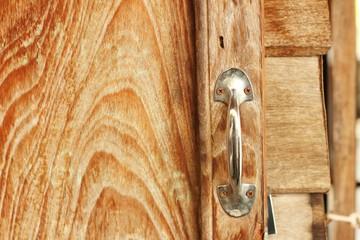 door handles on a brown wooden door.