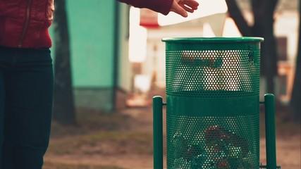 Woman Throws Trash in Dustbin