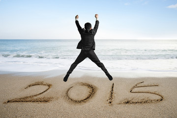 Jumping businessman cheering for new year 2015 on sand beach
