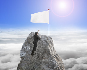 Businessman hand wanting for white flag on peak with sunlight
