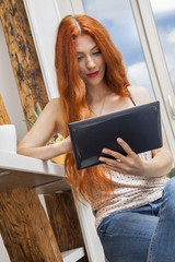 Sitting Woman with a Glass of Drink and a Tablet
