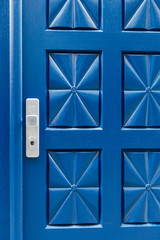 Closed blue door with pattern and aluminium handle