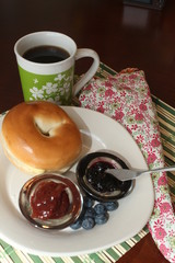 Bagel with a variety of jellies and a cup of coffee