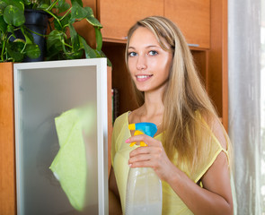Blonde girl cleaning glass door of furniture